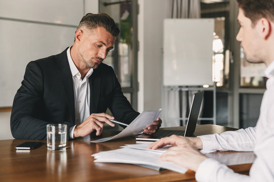 Business, career and placement concept - caucasian businessman 30s negotiating with male employer and reading his resume during job interview in office