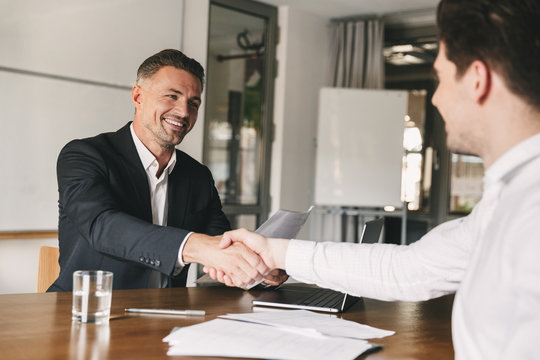 Business, career and placement concept - joyful handsome businessman 30s smiling and shaking hands with male candidate, who was recruited during interview in office