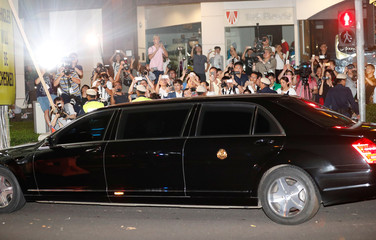 Journalists and bystanders take pictures of North Korean leader Kim Jong Un's vehicle as he arrives to the St Regis hotel after a late night sightseeing tour in Singapore