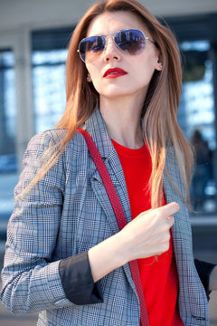 A woman with a red lipstick and a red bag in the city on the street next to the shopping center. Street style