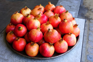 Platter of pink and red pomegranates for sale at a fruit market