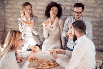 Happy young business team eating pizza in office