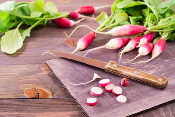 Fresh ripe radish cut into pieces on a cutting board and kitchen knife on a wooden table