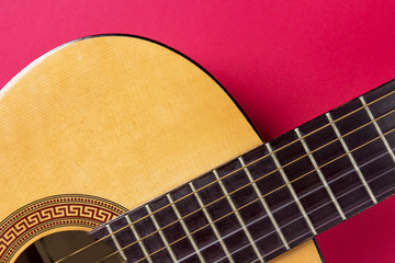 Acoustic guitar close-up on a pink background. Music hobby concept.