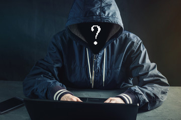 Anonymous hacker programmer uses a laptop to hack the system. Stealing personal data. Concept of cyber crime