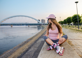 Roller girl resting after drive, sitting on concrete wall