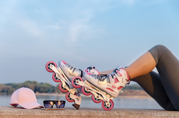 Closeup female legs with roller skates , cap and sunglasses, summer sports activity and relaxation concept
