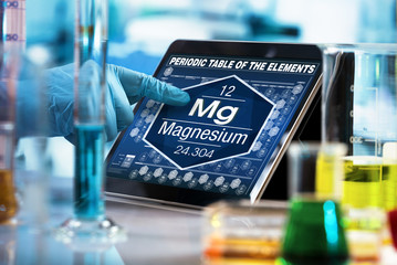 scientist consulting on the digital tablet data of the chemical element Magnesium Mg / researcher working on the computer with the periodic table of elements