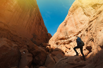Beautiful woman with backpack hiking along a scenic canyon overlook in Arches National Park in Utah