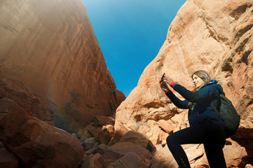 Female photographer takes picture with rock formation in the Arches National Park, Utah, USA