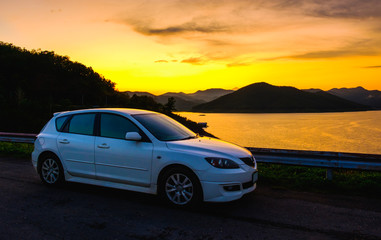White sport car parking at dam in sunset and sunrise