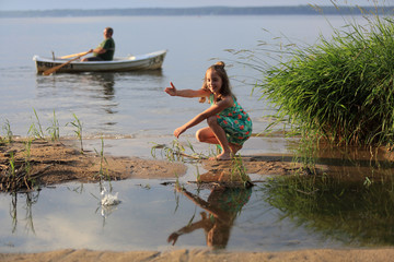 Fototapeta Uśmiechnięta dziewczynka wrzuca kamienie do wody jeziora, mężczyzna na łodzi.