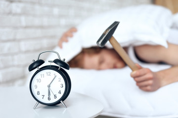 Young red haired man hammers alarm clock. Wall mural