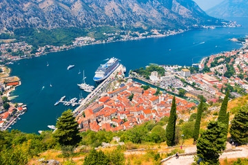 Bay of Kotor with old town and cruise ship in port. Aerial view of coastal town in Montenegro.