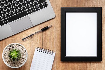 Empty black frame on a wooden desk with a laptop, a notebook and a cactus