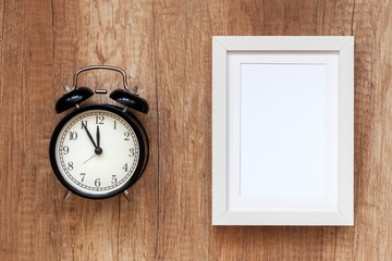 Empty white frame and black clock from above on a wooden countertop