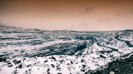 Industrial explosion in a quarry for the extraction of iron ore. Winter season, panorama of the pit.
