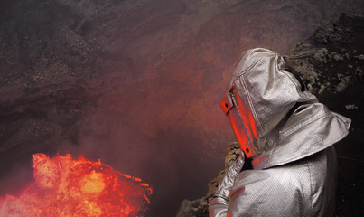 A volcanologist stands in dangerous proximity to a crater with molten lava in a thermo-suit