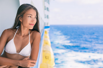 Cruise ship vacation bikini woman relaxing on deck. Asian girl in swimwear enjoying ocean view from boat in Caribbean travel holidays.