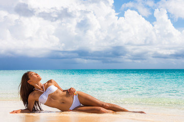 Sexy fashion bikini woman sunbathing lying down on white sand beach relaxing showing off toned abs and slim body. Asian model on tropical travel summer holidays