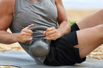 Kettlebell fitness man training stomach ab workout doing russian twist exercise with weight. Exercising on beach training with kettlebells working out core, obliques and abdominal muscles.