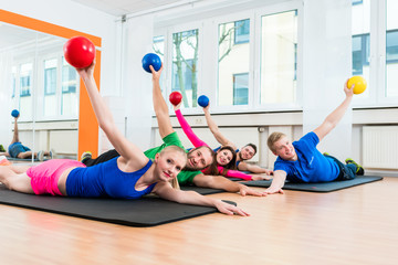 Men and women during floor exercises on yoga mats using medicine balls in gym