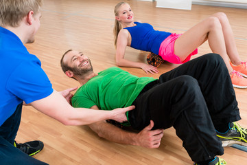 Man and women doing floor exercises with roll and get advise by  physiotherapist