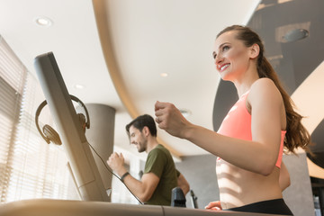 Happy young woman listening to music while running beside a handsome man on a modern treadmill with touch screen and headphones