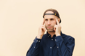 Pensive European male keeps fore fingers on temples, tries to concentrate and recollect his mind, isolated over beige studio background, dressed in fashionable clothes. Thoughtful hipster guy indoor