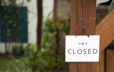 white closed sign on wood pole
