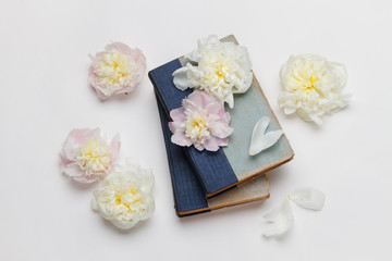 White and pink peonies and old books on white background