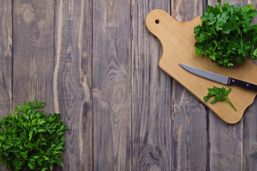 Fresh parsley on a cutting board and a knife. cooking. Healthy eating. Greenery. Top view. The concept of a healthy diet.