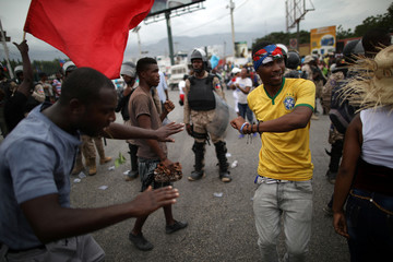 Two men dance as workers gather to protest in Port-au-Prince