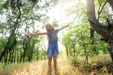 Happy little girl raises hands to the sun. Full length portrait
