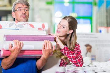 Heimwerker-Paar, Mann und Frau, kauft viele Rollen Tapete im Baumarkt für Do-it-yourself-Projekt