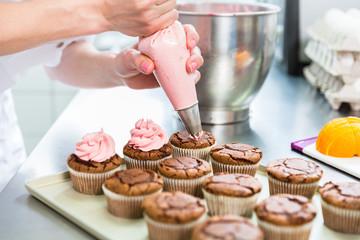 Frauen in Konditorei verzieren Cupcakes mit Spritzbeutel