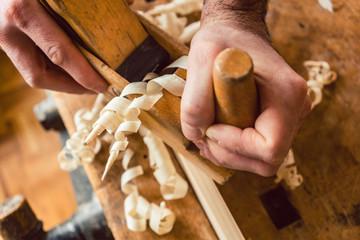 Draufsicht auf Hand von Tischler der mit Hobel an Brett arbeitet