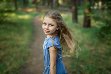 Portrait of little girl looks back in the forest