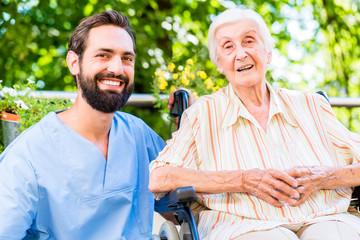 Altenpfleger unterhält sich mit Seniorin im Heim