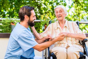 Pfleger hält Hand von Seniorin im Seniorenheim