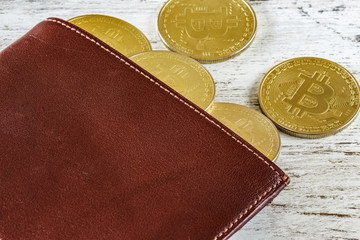 Metal bitcoins in brown leather wallet. Bitcoin - modern virtual coins. Block chain technology