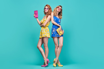 Wall Mural - Two Model Woman in Stylish Trendy Summer Outfit. Young Beautiful Pretty Lady in Fashion pose. Wavy Hairstyle, Sunglasses. Playful Slim Girls in Glamour Heels. Creative