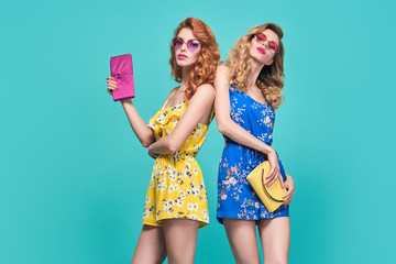 Wall Mural - Two Young woman in Floral Dress. Trendy wavy Hairstyle. Glamour Sexy Blond Redhead Model in fashion pose, Stylish Sunglasses, Clutch. Playful Summer Girl on Blue