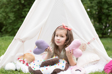 Little girl lying and playing in a tent, children's house wigwam in park. Happy mothers day. Child with big donuts and heart-shaped pillows. Summer, childhood concept.