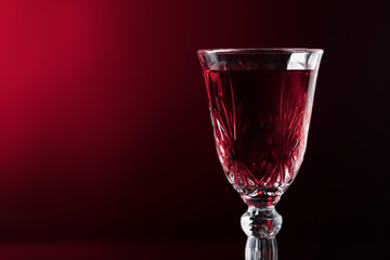 Close-up of crystal glass with red wine on dark background.