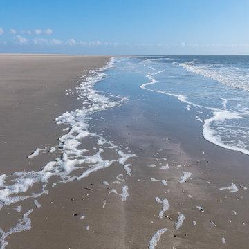 Strand an der Nordsee mit auslaufenden Wellen, flach und weit bei Sonnenschein