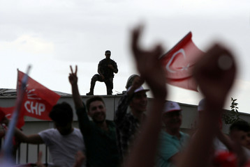 A member of Turkish police special forces stands guard as supporters of Muharrem Ince, presidential candidate of the main opposition CHP, wave Turkish and party flags during an election rally in Diyarbakir
