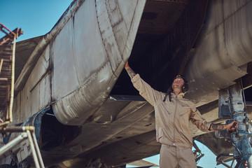 Mechanic in uniform carries out maintenance of a war fighter-interceptor in an open-air museum.