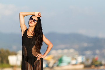 Beauty young woman with long dark hair in black swimwear and transparent dress. concept of happy holiday and resort time