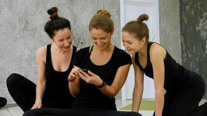 Three young women surfing internet using smartphone after workout at yoga class